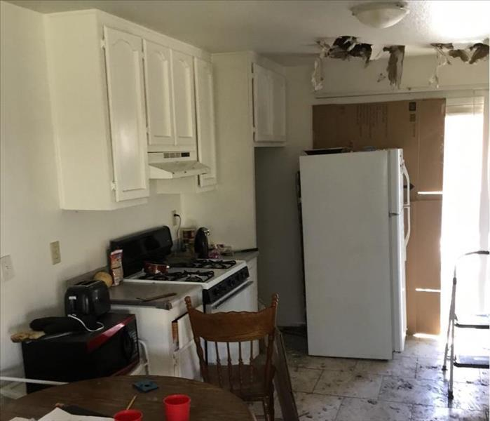 Fire damage in Apple Valley home kitchen. There are holes in the ceiling, soot and ash cover the floor.