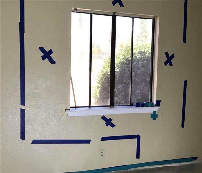 White wall marked with blue x's for drywall removal